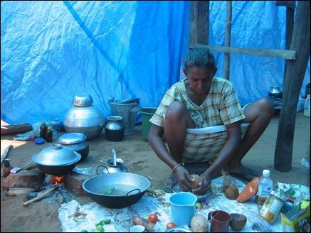 Vincent Daisy (44), wife of a fisherman and mother of two, cooks lunch in a welfare camp in Thampattai in the afternoon. She says she received only rice, sugar and flour from relief workers and have to buy vegetables, chillie powder, onion, green chillies, coconut and other spices at the shop. She earns Rs 300 clearing rubble. She says she is sick after working for long hours in the heat and finds difficult to make ends meet after her husband lost his job in Tsunami.  The tent they are living in is very hot that no one can stay inside more than a few minutes. Some camp residents are using coconut fronds as roof to make the tents cooler.