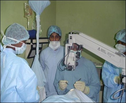 British eye surgeon, Dr Puvanachanthiran, helping staff with the intricacies of performing eye surgery.