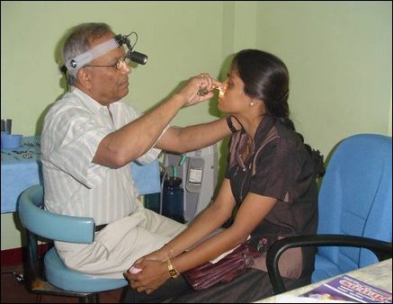 Dr Jeyalingam, an ENT surgeon from New York examines the eyes of a female patient at the Dr Ponnambalam Memorial Hospital.