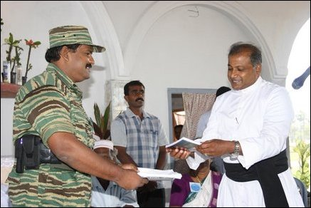 A book containing narratives by a young journalist Mr. Logeesan was released at the Church. Special Commander of the Sea Tigers, Col. Soosai is handing over the first copy of the book to Rev. James Pathinathar