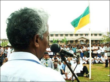 Sri Koneswara Hindu College Principal M.Rajaratnam presiding over the condolence meeting, College flag is seen half-mast with the college in background