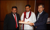 Pakistan's Ambassador [Right] hands over a cheque to Basil Rajapaksa and Rishad Bathiyutheen